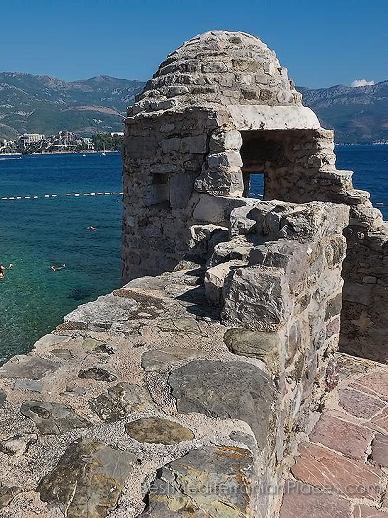 The loopholes of the tower of the old city fortifications look at bathing tourists