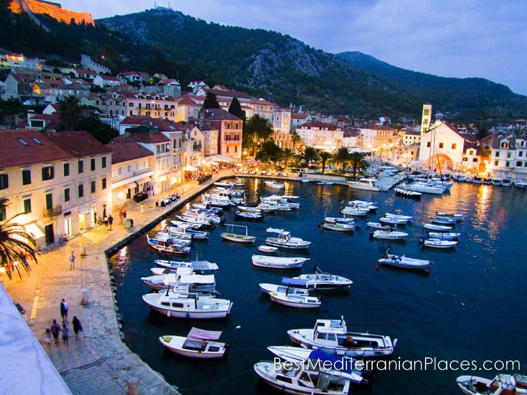 Night lights of the city of Hvar are reflected in the calm surface of the marina