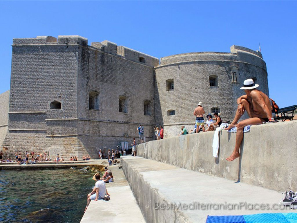 Some tourists prefer to catch the sun's rays directly at the marina at the fortress of Dubrovnik old town